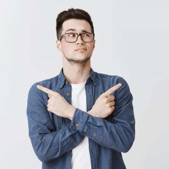 Waist-up shot of hesitant unsure attractive caucasian young man with bristle in glasses and blue shirt crossing hands on chest, pointing sideways as being doubtful what chose, looking right unsure.